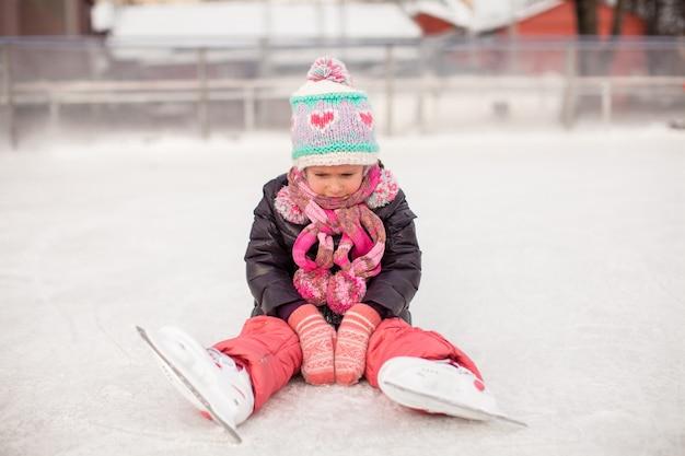 Menina triste sentada em um rinque de patinação após a queda Foto Premium