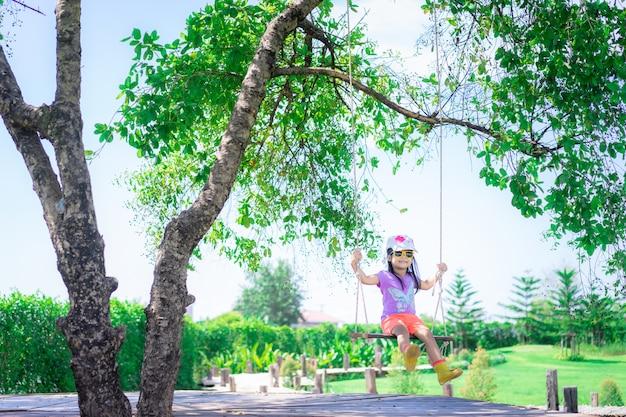 Menina usa chapéu e óculos de sol sentado em um balanço no parque Foto Premium