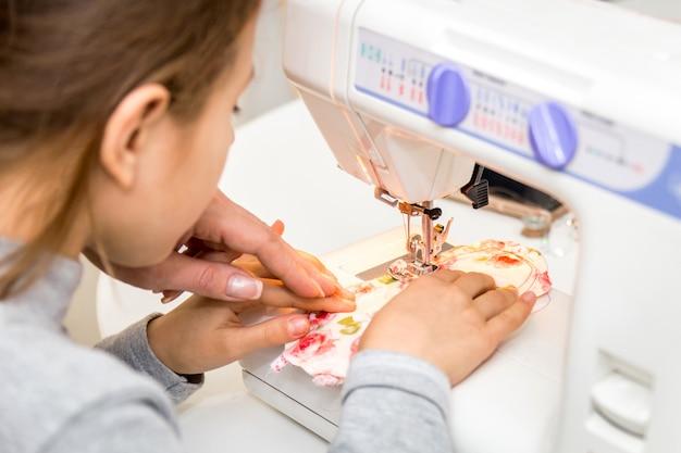 Menina usando a máquina de costura para fazer artesanato Foto Premium