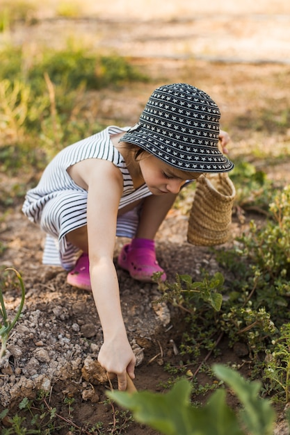 Menina usando chapéu agachado na horta Foto gratuita