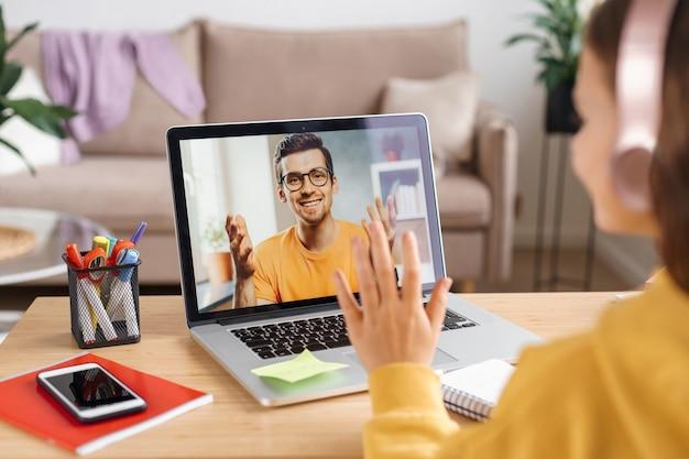 Menina usando fones de ouvido e laptop para aprender aulas on-line com o professor pela internet remota Foto Premium