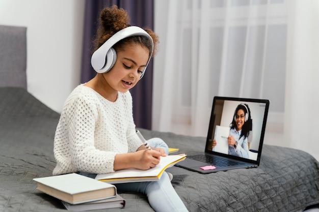 Menina usando laptop para escola online Foto gratuita