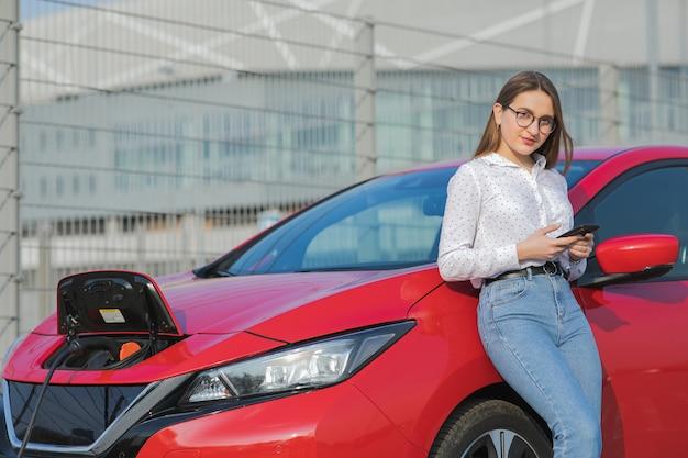 Menina usando telefone inteligente e fonte de alimentação em espera conectar a veículos elétricos para carregar a bateria no carro. carro ecológico conectado e carregando baterias Foto Premium