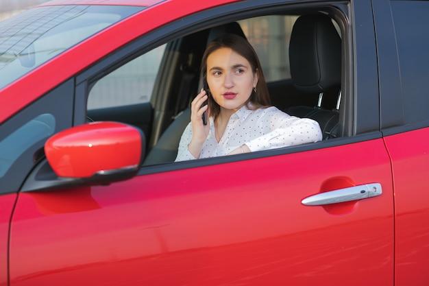 Menina usando telefone inteligente e fonte de alimentação em espera conectar a veículos elétricos para carregar a bateria no carro. jovem positiva falando ao telefone senta-se no carro elétrico e carregamento. Foto Premium