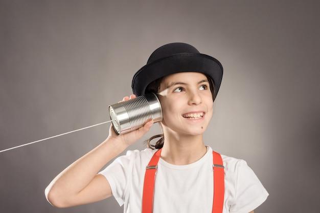 Menina usando uma lata como telefone em cinza Foto Premium