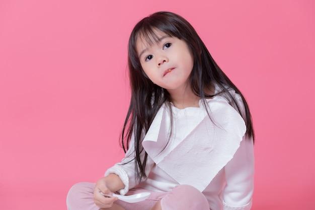 Menina vai comer comida por colher de plástico com um lenço de papel feito em um avental na parede rosa. Foto Premium