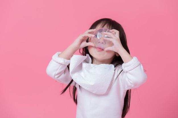 Menina vai comer comida por grande golpe com um lenço de papel feito em um avental na parede rosa. Foto Premium