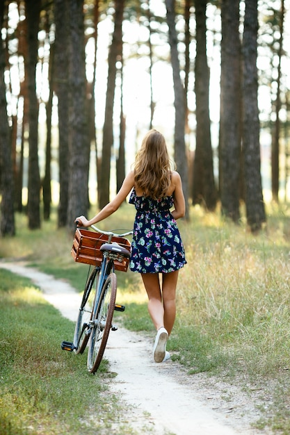 Menina vai em uma ciclovia na floresta Foto gratuita