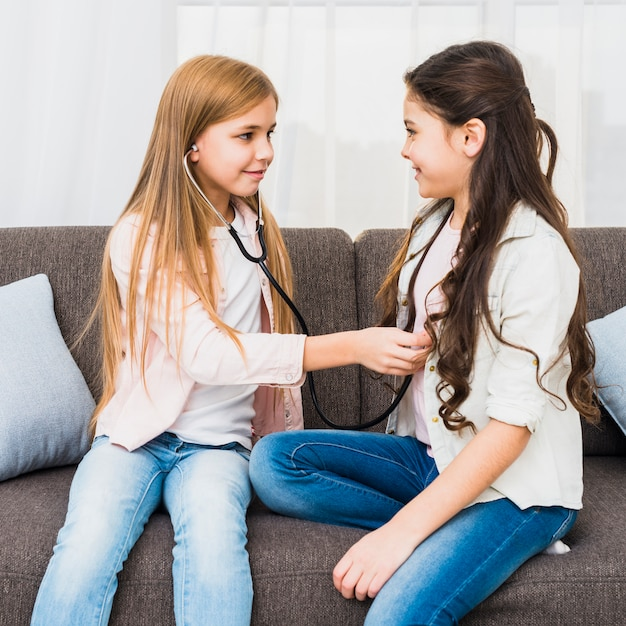 Menina, verificar, dela, amigo, batida coração, com, estetoscópio, sentar sofá Foto gratuita