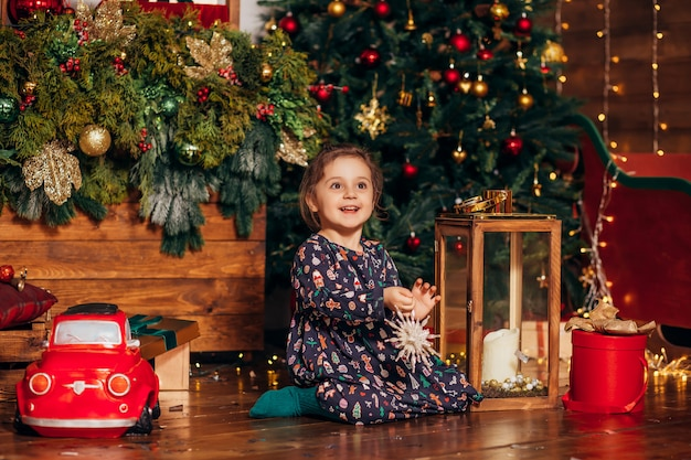 Menina veste árvore de natal em casa Foto Premium