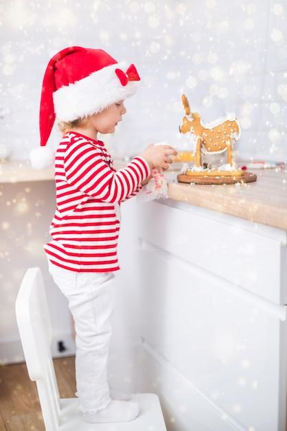 Menina vestida de natal com presentes perto da árvore de natal bebe leite e decora um cervo Foto Premium