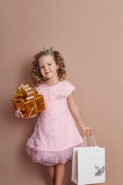 Menina vestido rosa detém o pacote de caixa de presente de ouro Foto Premium
