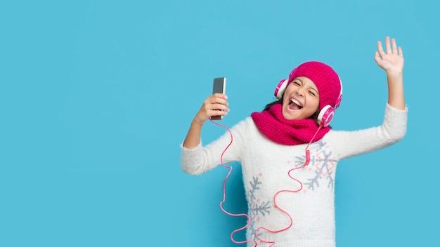 Menina vestindo roupas de inverno, ouvir música Foto gratuita