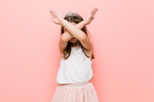 Menina vestindo um olhar de princesa, mantendo os dois braços cruzados, negação. Foto Premium
