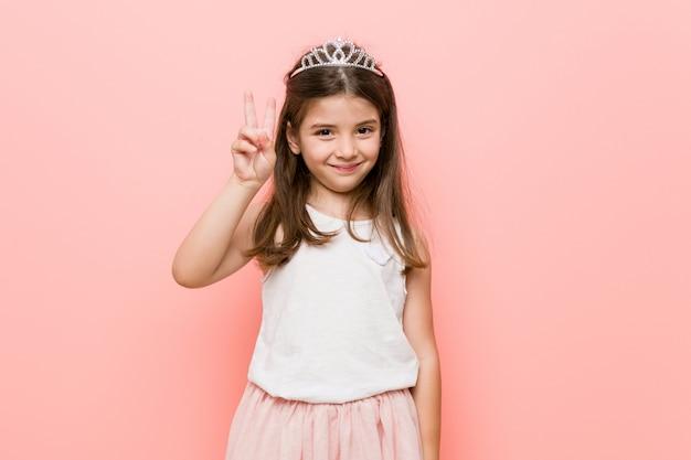 Menina vestindo um olhar de princesa mostrando o número dois com os dedos. Foto Premium