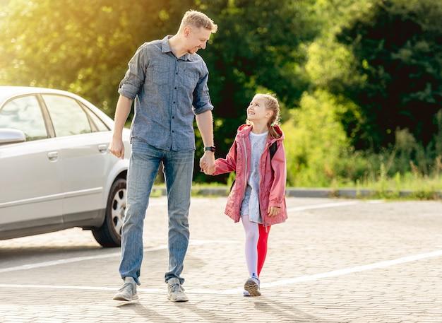 Menina voltando para a escola de mãos dadas com o pai Foto Premium