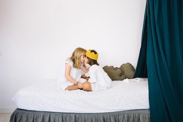 Meninas abraçando na cama Foto gratuita