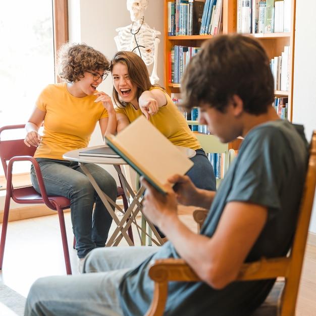 Meninas adolescentes rindo e apontando para o menino de leitura Foto gratuita