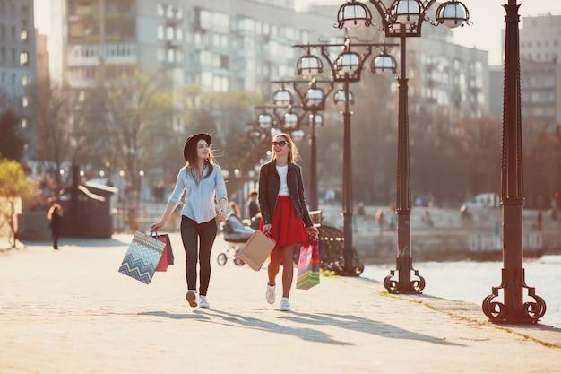 Meninas andando com as compras nas ruas da cidade Foto gratuita