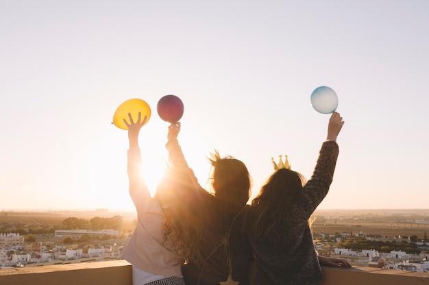 Meninas anônimas com balões no telhado Foto gratuita