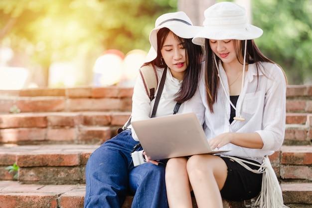 Meninas asiáticas jovens e amigos viajante na cidade, duas mulheres sentadas usam busca laptop para atrações Foto Premium