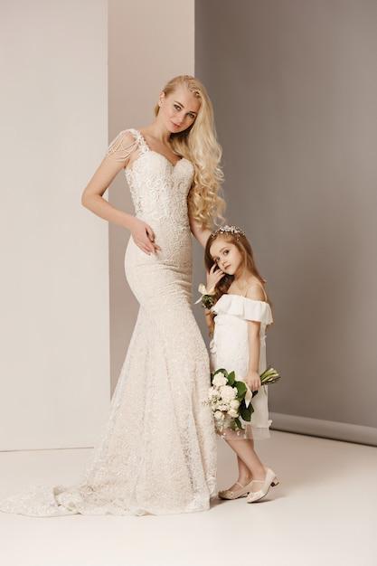 Meninas bonitas com flores vestidas em vestidos de noiva Foto gratuita
