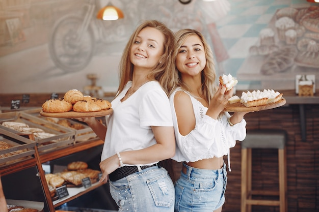 Meninas bonitas compra pães na padaria Foto gratuita