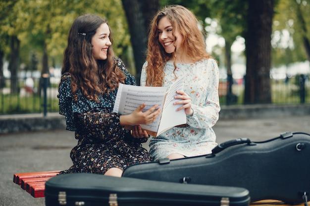 Meninas bonitas e românticas em um parque com um violino Foto gratuita