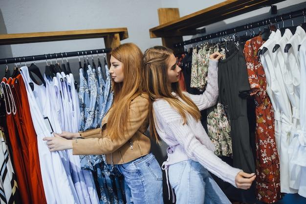 Meninas bonitas em compras, escolhendo roupas na loja Foto Premium