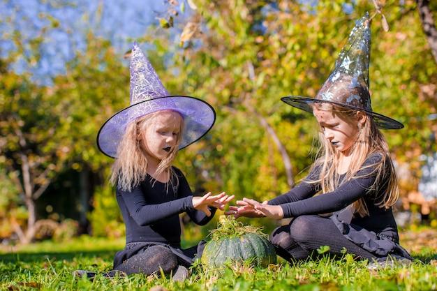 Meninas bonitos pouco lançando um feitiço no halloween em traje de bruxa Foto Premium
