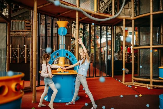 Meninas brincam com metralhadora, centro de jogos infantis Foto Premium