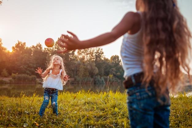 Meninas brincando com bola no parque de verão, crianças se divertindo Foto Premium