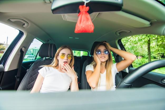 Meninas chocadas enquanto dirigia um carro. férias de verão Foto gratuita