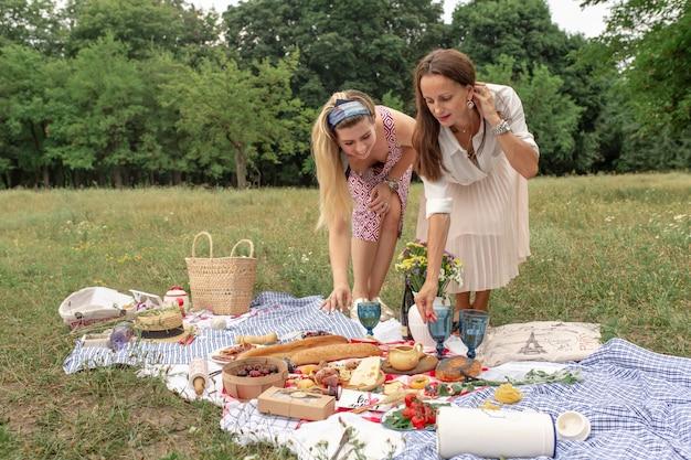Meninas, colocando a comida de piquenique em um cobertor de piquenique xadrez Foto Premium