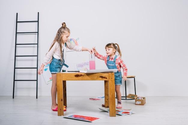 Meninas colocando pincéis em copo de água Foto gratuita