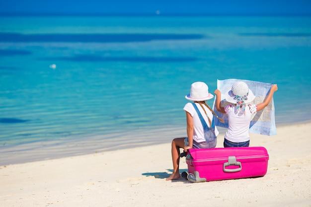 Meninas com mala grande e mapa na praia tropical Foto Premium