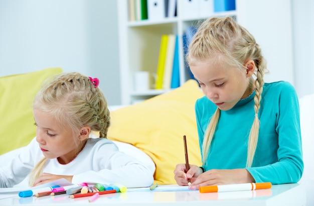 Meninas com muitos lápis de cor sobre a mesa Foto gratuita