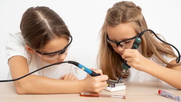 Meninas com óculos de proteção fazendo experimentos científicos Foto gratuita
