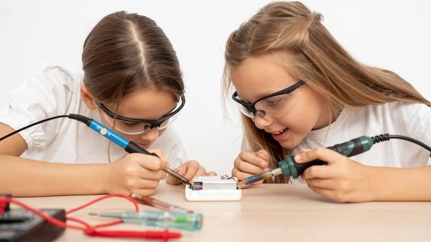 Meninas com óculos de segurança fazendo experimentos científicos juntas Foto gratuita