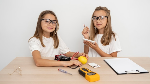 Meninas com óculos de segurança fazendo experimentos científicos Foto gratuita