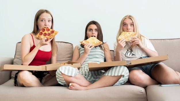 Meninas comendo pizza e assistindo a um filme de terror Foto gratuita