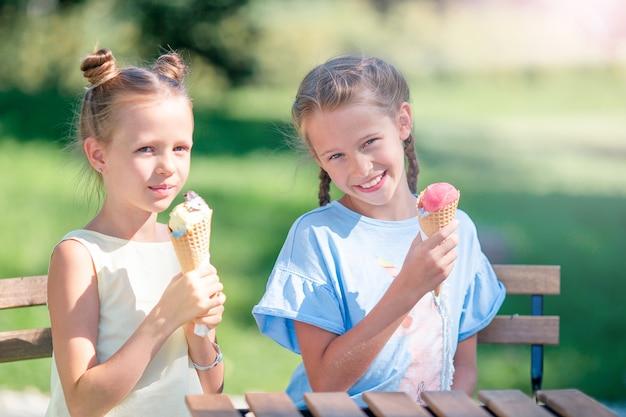 Meninas comendo sorvete ao ar livre no verão no café ao ar livre Foto Premium