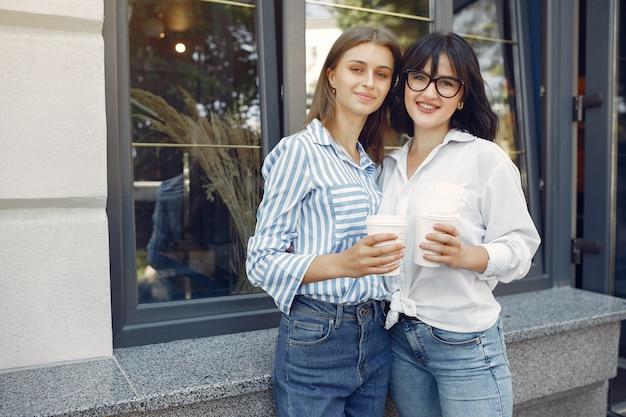 Meninas da moda em pé na rua Foto gratuita