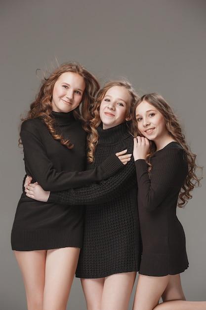 Meninas da moda juntos e olhando para a câmera sobre cinza Foto gratuita