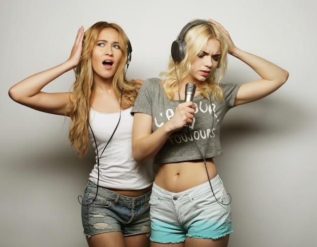 Meninas de beleza com um microfone, cantando e dançando Foto Premium