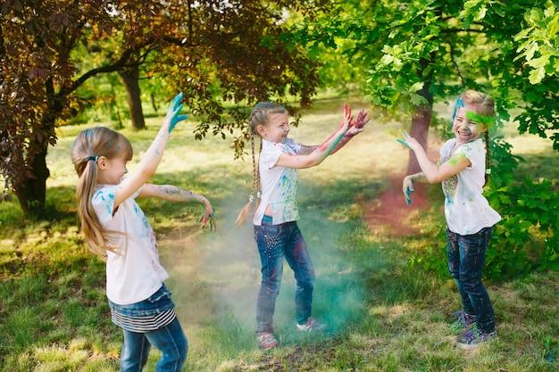Meninas de criança europeus bonitos comemoram o festival de holi indiano com pó de tinta colorida no rosto e no corpo Foto Premium
