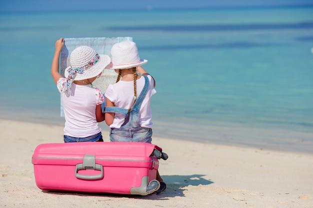 Meninas de turistas pouco com mala grande na praia tropical branca Foto Premium