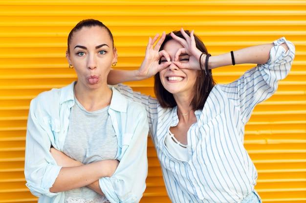 Meninas de vista frontal fazendo caretas enquanto olha para a câmera Foto gratuita