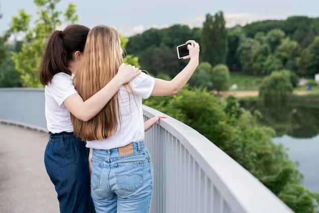 Meninas de vista traseira tomando uma selfie em uma ponte Foto gratuita