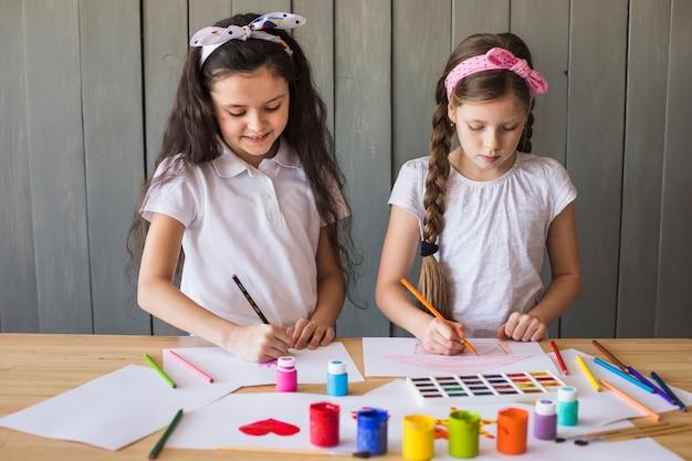Meninas desenhando com lápis de cor sobre papel branco sobre a mesa de madeira Foto gratuita